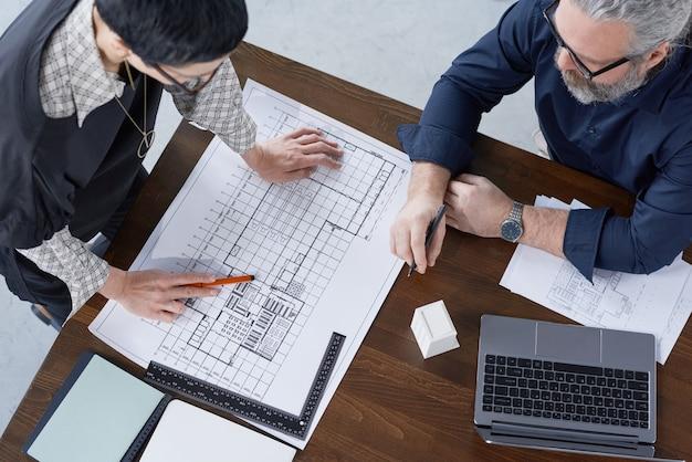 Hohe betrachtungswinkel von zwei ingenieuren, die das projekt eines neubaus am tisch im büro untersuchen
