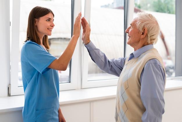 Hohe fiving pflegekraft der seitenansicht mit altem mann