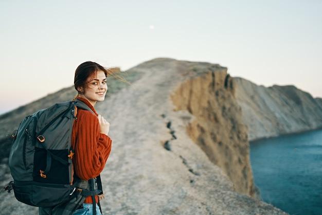 Hohe gebirgshügel und glücklicher reisender in der natur nahe dem meer