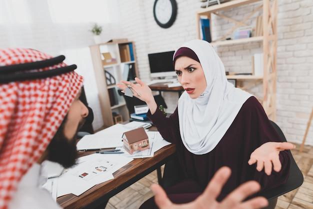 Hohe hypotheken-arabische familie, die im büro streitet