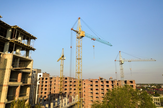 Hohe mehrstöckige wohnhäuser im bau. beton- und ziegelrahmen von hochhäusern. immobilienentwicklung im stadtgebiet.