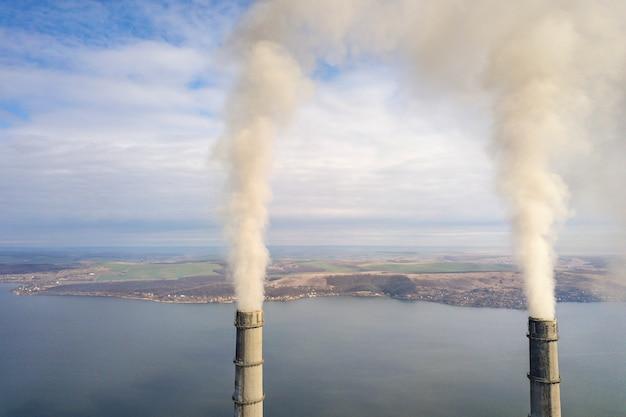 Hohe rohre des kraftwerks, weißer rauch auf ländlicher landschaft, seewasser und blauer himmel kopieren raumhintergrund.