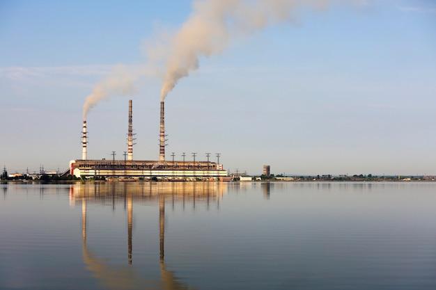 Hohe rohre des wärmekraftwerks mit dickem rauch, der sich in der wasseroberfläche widerspiegelt. umweltverschmutzungskonzept.