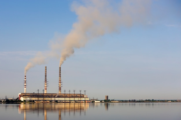 Hohe rohre des wärmekraftwerks mit starkem rauch reflektierten sich in lke wasseroberfläche. verschmutzung des umweltkonzeptes.