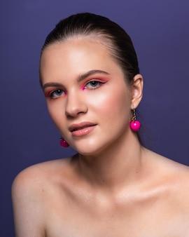 Hohe schönheitsfoto eines reizenden jungen mädchens mit wunderbarem professionellem make-up, runden rosa ohrringen, mit langen braunen haaren. posieren über blauem hintergrund. nahansicht. studioaufnahme. porträt