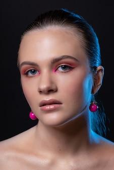Hohe schönheitsfoto eines reizenden jungen mädchens mit wunderbarem professionellem make-up, runden rosa ohrringen, mit langen braunen haaren. posieren über schwarzem hintergrund. nahansicht. studioaufnahme. porträt