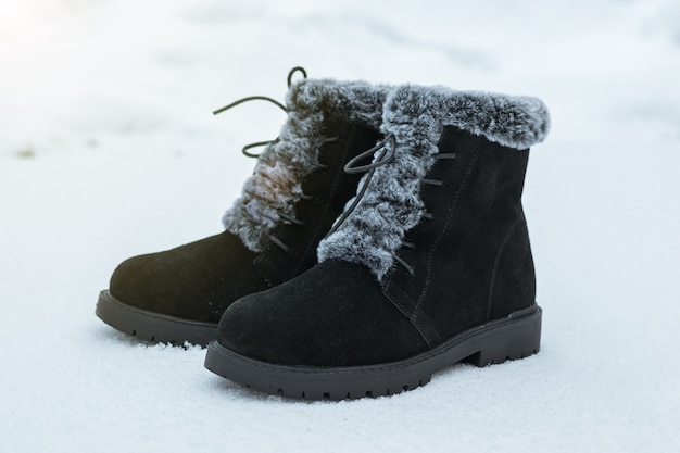 Hohe schwarze modische damenstiefel auf dem ersten schnee. schöne und praktische damen winterschuhe.