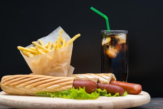 Hohe soda mit eis und hotdogs eingewickelt in brot und salat neben pommes vor schwarzem hintergrund