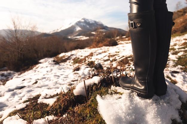 Hohe stiefel der frau an einem schneebedeckten berg