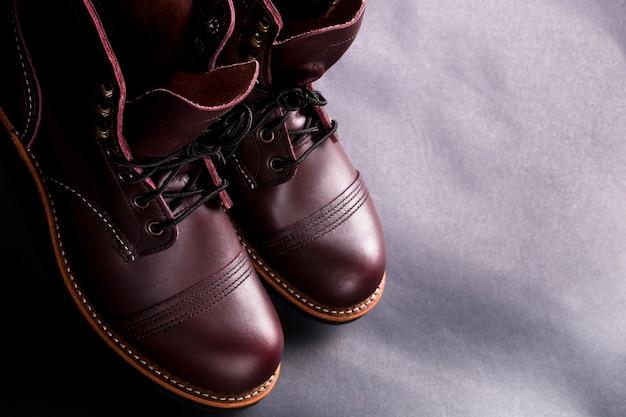 Hohe stiefel. modische braune herrenlederschuhe auf hellschwarzem hintergrund. draufsicht. speicherplatz kopieren.