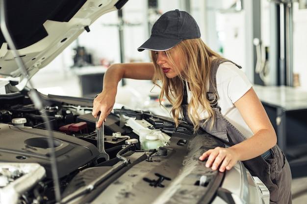 Hohe winkel mechaniker weibliches auto repariert