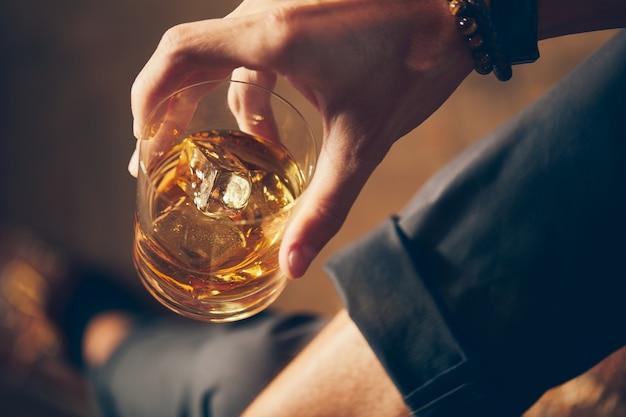 Hohe winkel-nahaufnahmeaufnahme eines mannes, der ein glas whisky hält
