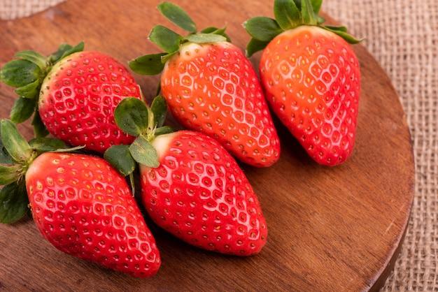 Hohe winkel-nahaufnahmeaufnahme von frischen erdbeeren auf einem runden hölzernen schreibtisch