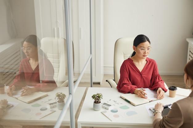 Hohe winkelansicht an der modernen asiatischen geschäftsfrau, die mit kunden spricht, während am schreibtisch in der weißen bürokabine, kopienraum arbeitet