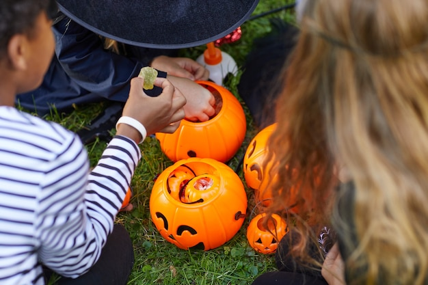 Hohe winkelansicht bei gruppe von kindern, die kostüme tragen, die süßigkeiten von halloween-eimern im freien nehmen, raum kopieren