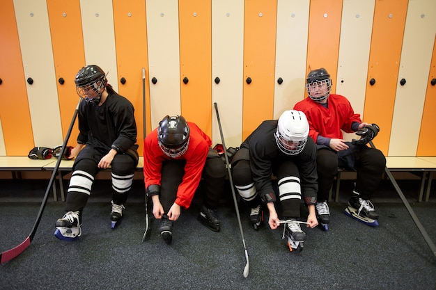 Hohe winkelansicht bei weiblicher eishockeymannschaft, die ausrüstung anlegt