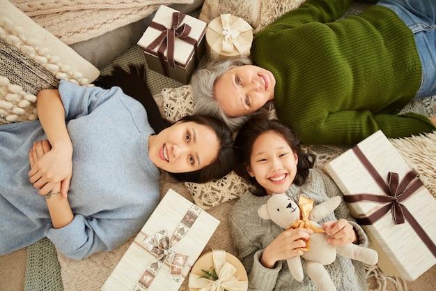 Hohe winkelansicht der asiatischen familiengeneration, die auf dem boden zwischen geschenken und spielzeugen liegt und lächelt