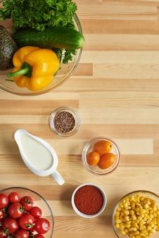 Hohe winkelansicht der gewürze des frischen gemüses und anderer bestandteile auf dem holztisch zum kochen