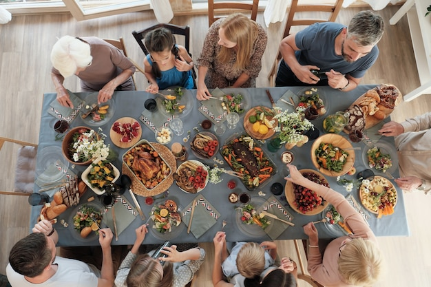 Hohe winkelansicht der großen familie, die am tisch sitzt und zu hause zusammen zu abend isst