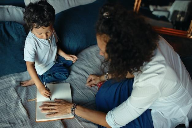 Hohe winkelansicht der jungen dunkelhäutigen frau mit dem lockigen haar, das auf bett mit hand auf blatt im heft sitzt, zeichnung des kleinen jungen, zeichnen umriss ihrer handfläche.