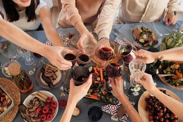 Hohe winkelansicht der leute, die am festlichen tisch sitzen, der zu abend isst und mit gläsern rotwein röstet
