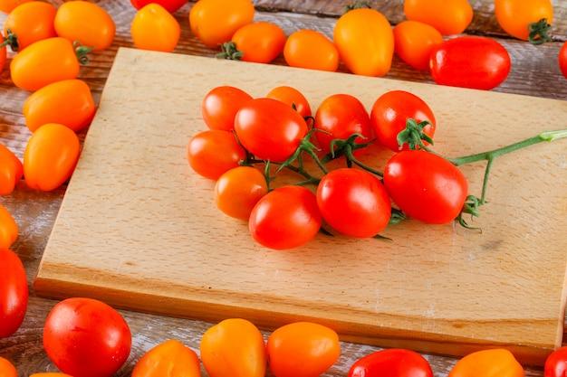 Hohe winkelansicht der mini-tomaten auf holz und schneidebrett