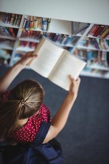 Hohe winkelansicht des aufmerksamen schulmädchen-lesebuchs in der bibliothek