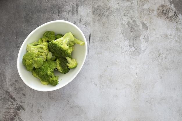 Hohe winkelansicht des brokkolis in einer weißen schüssel auf dem tisch