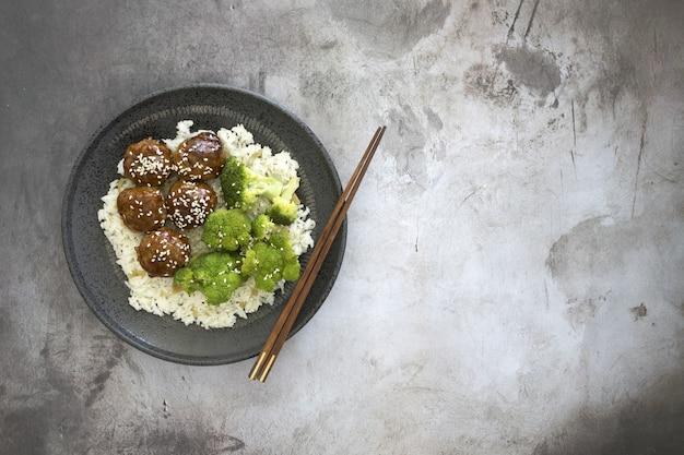 Hohe winkelansicht des gekochten reises mit fleischbällchen und brokkoli in einem teller auf dem tisch mit stäbchen