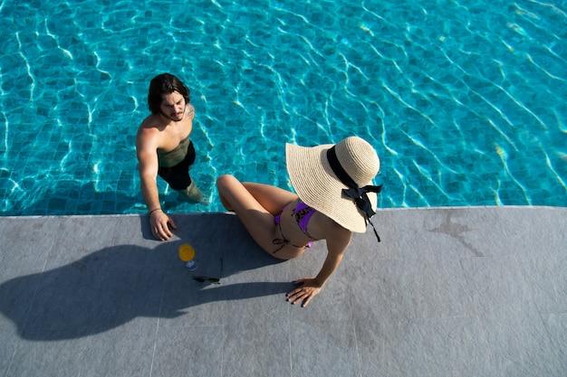 Hohe winkelansicht des glücklichen jungen paares durch den pool. paar entspannen sich auf der poolparty. sommerferienkonzept