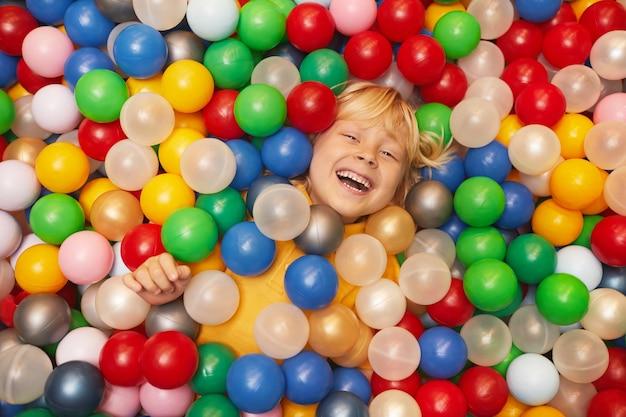 Hohe winkelansicht des glücklichen kleinen jungen, der mit farbigen bällen spielt