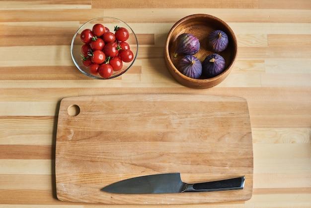 Hohe winkelansicht des hölzernen schneidebretts mit messer mit tomaten und feigen in den schalen auf dem tisch