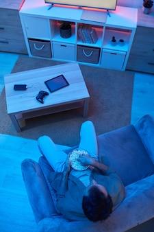 Hohe winkelansicht des jungen mannes, der auf sofa sitzt, popcorn isst und film im fernsehen im dunklen raum sieht
