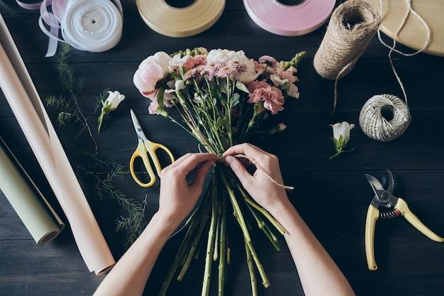 Hohe winkelansicht des nicht erkennbaren floristen, der durch holztisch mit blumenstraußverpackungsgegenständen steht und blumen mit schnur bindet