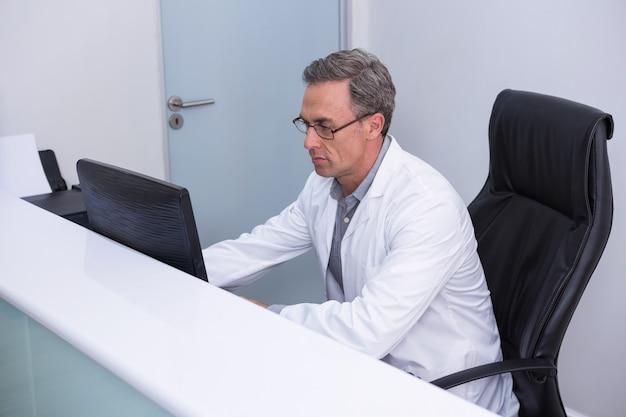 Hohe winkelansicht des zahnarztes, der durch computer sitzt