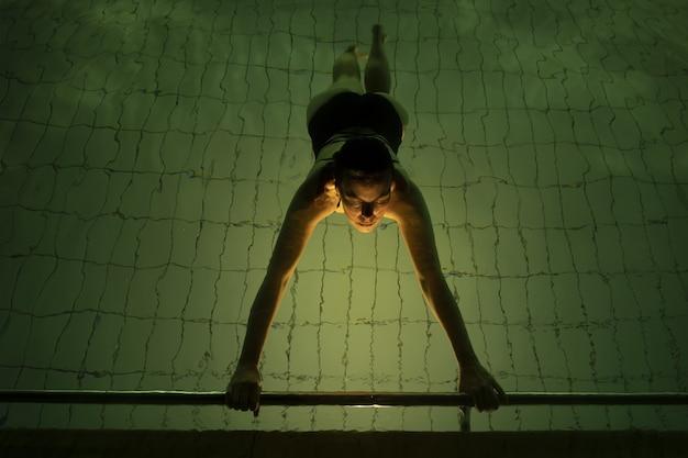 Hohe winkelansicht einer frau, die in einem pool unter den lichtern schwimmt - perfekt für sportkonzepte