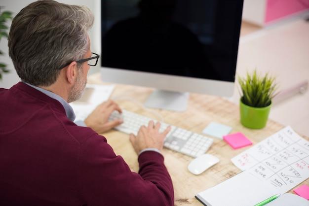Hohe winkelansicht eines mannes, der am computer arbeitet