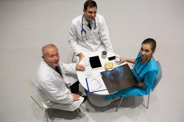 Hohe winkelansicht von ärzten und chirurgen, die röntgen während des frühstücks untersuchen