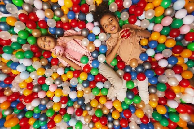 Hohe winkelansicht von kleinen kindern, die zusammen im pool liegen und mit farbigen bällen spielen