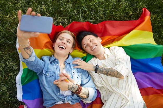 Hohe winkelansicht von zwei lesben, die auf farbiger flagge liegen und selfie-porträt auf handy im freien machen