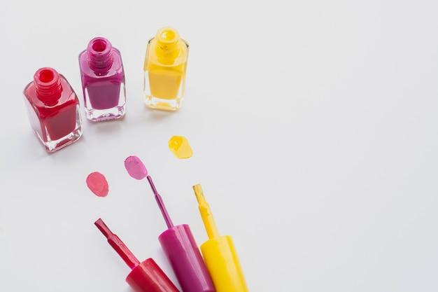 Hohe winkeldekoration mit nagellacken auf weißem hintergrund