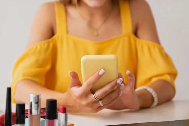 Hohe winkelfrau am schreibtisch unter verwendung des mobiles