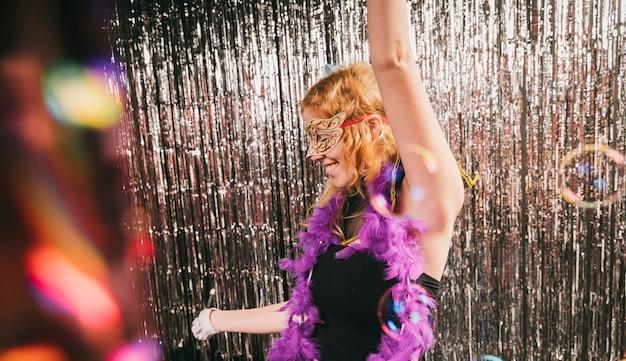 Hohe winkelfrau an der karnevalsparty, die spaß hat