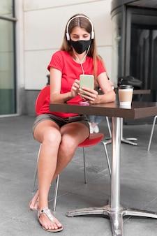 Hohe winkelfrau an der terrasse mit maske