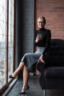 Hohe winkelfrau auf couch mit mobile