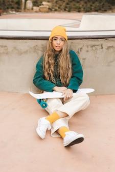 Hohe winkelfrau auf fußboden mit skateboard
