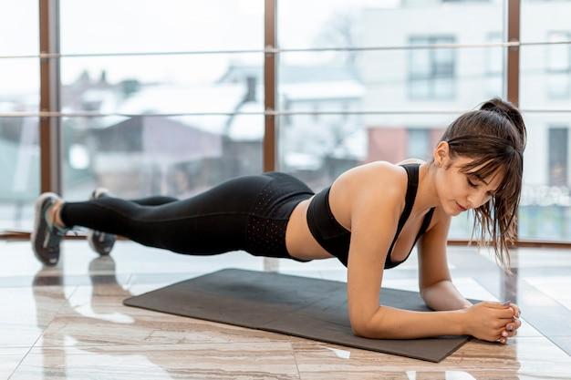 Hohe winkelfrau auf matte auf yogaposition