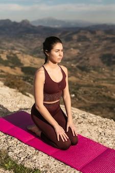 Hohe winkelfrau auf übendem yoga der matte