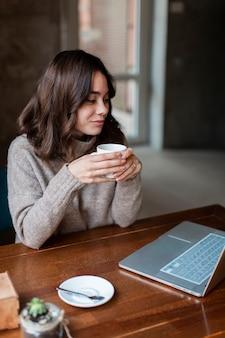 Hohe winkelfrau, die an laptop arbeitet