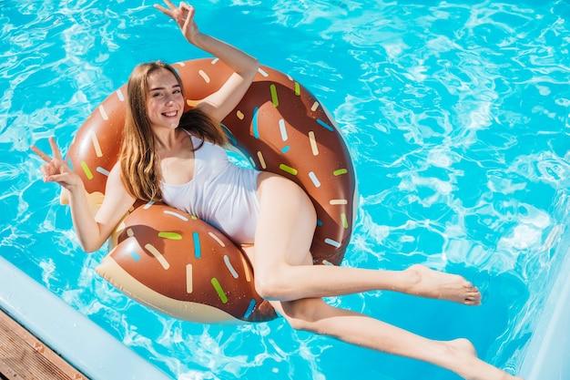 Hohe winkelfrau, die auf donutschwimmenring aufwirft